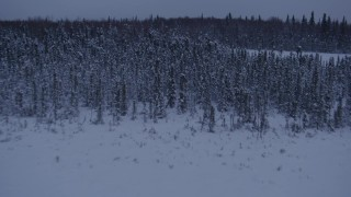 AK0001_1681 - 4K stock footage aerial video flying over frozen, snowy ground and woods at twilight in Point MacKenzie, Alaska, reveal Downtown Anchorage