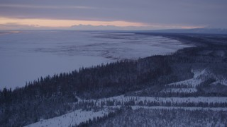AK0001_1692 - 4K stock footage aerial video following snowy, wooded shore of Point MacKenzie at twilight, Alaska