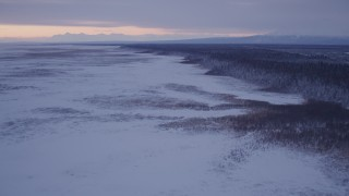 AK0001_1695 - 4K stock footage aerial video flying over frozen, snow covered ground at twilight, Point MacKenzie, Alaska