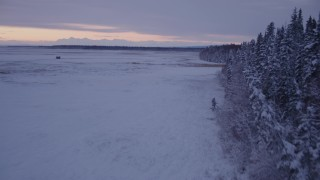 AK0001_1698 - 4K stock footage aerial video flying low over frozen, snow covered ground at twilight, Point MacKenzie, Alaska