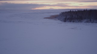 AK0001_1700 - 4K stock footage aerial video descending low over frozen, snowy ground at twilight, Point MacKenzie, Alaska