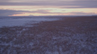 AK0001_1701 - 4K stock footage aerial video flying low over frozen, snowy ground and grass at twilight, Point MacKenzie, Alaska