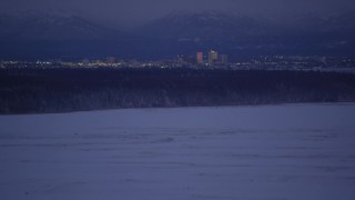 AK0001_1714 - 4K stock footage aerial video tilt up from snowy ground revealing Downtown Anchorage skyline, Alaska, night