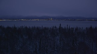 AK0001_1718 - 4K stock footage aerial video ascend from snowy trees, reveal Downtown Anchorage, Alaska, night