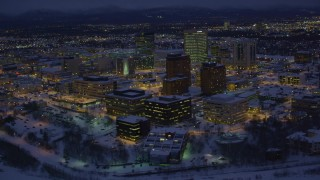 AK0001_1723 - 4K stock footage aerial video orbiting snow covered Downtown Anchorage at night, Alaska