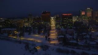 AK0001_1727 - 4K stock footage aerial video flying along icy shore of Cook Inlet, snowy Downtown Anchorage, Alaska, night