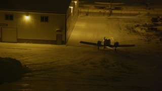 AK0001_1738 - 4K stock footage aerial video an airplane rounding hanger at snowy Merrill Field, Anchorage, Alaska, night