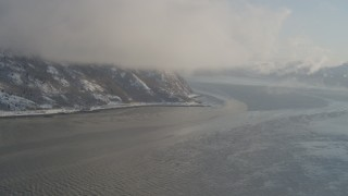 AK0001_1740 - 4K stock footage aerial video fly through low clouds over snowy Turnagain Arm of the Cook Inlet, Alaska