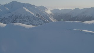 AK0001_1745 - 4K stock footage aerial video fly over snowy ridge, reveal wooded valleys between Chugach Mountains, Alaska