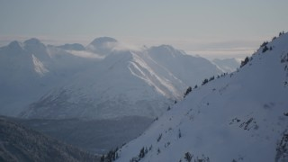 AK0001_1765 - 4K stock footage aerial video rounding a snowy slope revealing Carmen Lake, Chugach Mountains, Alaska