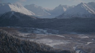 AK0001_1766 - 4K stock footage aerial video wooded slopes and river valley, tilt up to snow capped Chugach Mountains, Alaska