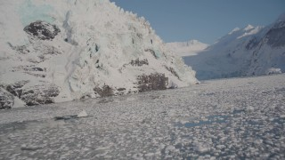 AK0001_1795 - 4K stock footage aerial video flying low over icy surface of Harriman Fjord toward snowy glacier, Alaska