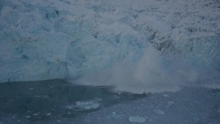AK0001_1811 - 4K stock footage aerial video ice breaking off of a snow covered glacier, Harriman Fjord, Alaska