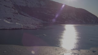 AK0001_1820 - 4K stock footage aerial video the sun reflecting off water in Harriman Fjord near snow covered glacier, Alaska