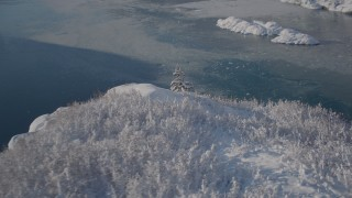 AK0001_1825 - 4K stock footage aerial video flying down snow covered mountain slope toward water in Harriman Fjord, Alaska