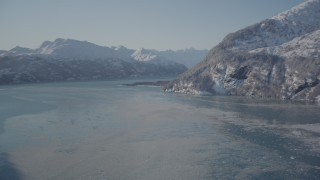 AK0001_1826 - 4K stock footage aerial video flying over icy water in Harriman Fjord surrounded by snowy mountains, Alaska