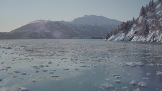 AK0001_1829 - 4K stock footage aerial video flying low over surface of Harriman Fjord bordered by snowy mountains, Alaska