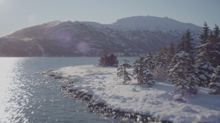 AK0001_1831 - 4K stock footage aerial video flying low over surface of Harriman Fjord, then over snowy, wooded shore, Alaska