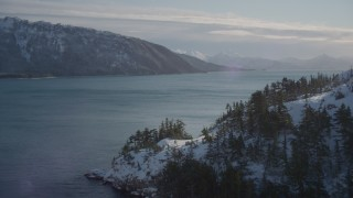 AK0001_1833 - 4K stock footage aerial video rounding a snowy shore in the Harriman Fjord, Alaska