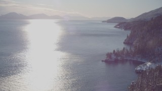 AK0001_1838 - 4K stock footage aerial video he sun reflecting off of water in Port Wells next to snowy, wooded shore, Alaska