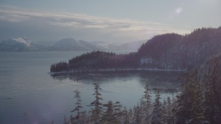 AK0001_1849 - 4K stock footage aerial video flying toward the snowy, wooded shore of a bay, Port Wells, Alaska