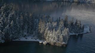 AK0001_1851 - 4K stock footage aerial video descending toward water near snowy, wooded peninsula, Port Wells, Alaska