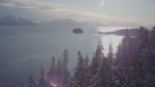 AK0001_1853 - 4K stock footage aerial video ascend snowy, wooded shore reveal Chugach Mountains, Port Wells, Alaska