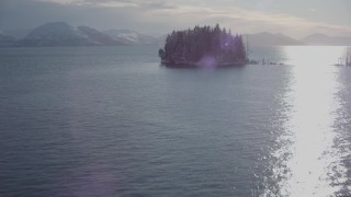 AK0001_1854 - 4K stock footage aerial video approach a tiny, wooded island, with a view of Chugach Mountains, Port Wells, Alaska