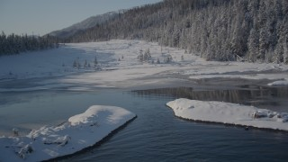 AK0001_1855 - 4K stock footage aerial video fly over icy shore beside snowy forest in Port Wells, Alaska