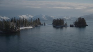 AK0001_1859 - 4K stock footage aerial video orbiting snow covered wooded islands in Port Wells, Alaska
