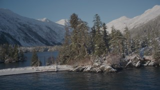 AK0001_1860 - 4K stock footage aerial video orbiting by a snowy, wooded mountain and small islands in Port Wells, Alaska