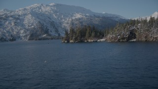 AK0001_1869 - 4K stock footage aerial video flying toward snowy, wooded shore, then reveal Bettles Bay, Port Wells, Alaska