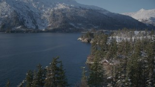 AK0001_1870 - 4K stock footage aerial video flying along snowy shore, rounding it to reveal Bettles Bay, Port Wells, Alaska