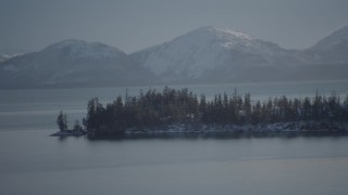 AK0001_1871 - 4K stock footage aerial video the evergreen trees and snow covered Chugach Mountains across Port Wells, Alaska