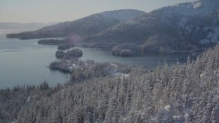 AK0001_1872 - 4K stock footage aerial video flying over snowy, wooded slopes, revealing Hummer Bay, Port Wells, Alaska