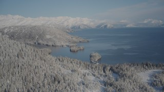 AK0001_1878 - 4K stock footage aerial video flying over snowy, wooded shore away from Hummer Bay, Port Wells, Alaska