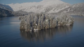 AK0001_1881 - 4K stock footage aerial video rounding a snowy, wooded island in Hummer Bay, Port Wells, Alaska