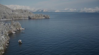 AK0001_1883 - 4K stock footage aerial video flying by small islands toward snowy, wooded shore, Port Wells, Alaska