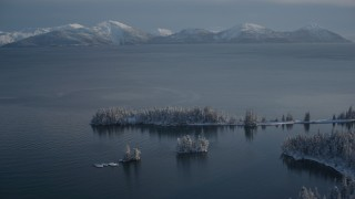 AK0001_1885 - 4K stock footage aerial video fly over snowy, wooded shore, Chugach Mountains across Port Wells, Alaska