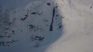 AK0001_1892 - 4K stock footage aerial video approaching a waterfall on a snowy mountain, Chugach Mountains, Alaska