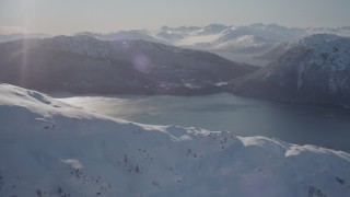 AK0001_1895 - 4K stock footage aerial video flying over snow covered mountain toward Pigot Bay, Alaska