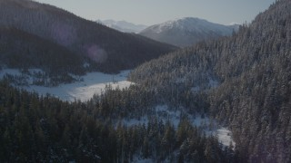 AK0001_1898 - 4K stock footage aerial video flying over snowy shore of Pigot Bay toward forested slopes, Alaska