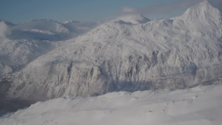 AK0001_1910 - 4K stock footage aerial video flying over a snowy summit toward Chugach Mountains, Passage Canal, Alaska
