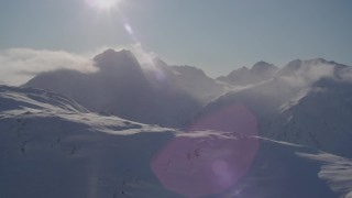 AK0001_1918 - 4K stock footage aerial video low clouds over snowy summits with sun overhead, Chugach Mountains, Alaska