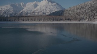 AK0001_1924 - 4K aerial stock footage video flying over surface of Carmen Lake approaching snow covered shore, Alaska