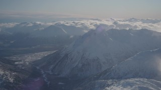 AK0001_1936 - 4K stock footage aerial video flying by a river valley surrounded by snowy Chugach Mountains, Alaska