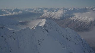 AK0001_1937 - 4K stock footage aerial video fly by snowy mountain range reveal, wooded valley, Chugach Mountains, Alaska