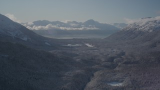 AK0001_1956 - 4K stock footage aerial video flying over a wooded valley between snowy Chugach Mountains, Girdwood, Alaska