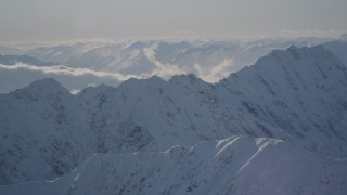AK0001_1975 - 4K stock footage aerial video snow covered mountain ranges and low clouds in Chugach Mountains, Alaska