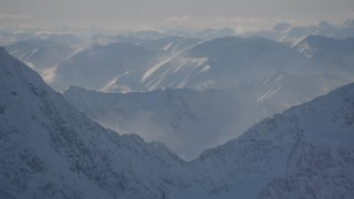 AK0001_1976 - 4K stock footage aerial video snow covered windblown mountains and low clouds in Kenai Mountains, Alaska